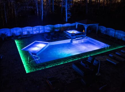 Luxury Backyard Geometric Pool with Spa at Night with Lights